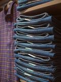 Kledende opslag Gevouwen jeans op plank op achtergrond van geruit Stock Afbeelding