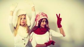Kleding die van de twee meisjes de warme winter pret hebben Stock Foto's