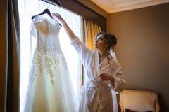 Kleding van het bruid de hangende huwelijk op een hanger dichtbij venster Royalty-vrije Stock Afbeelding