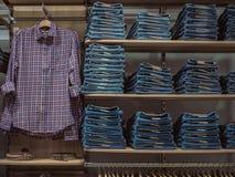 Kledingstukken van het rek de modieuze denim Toevallige kledingsstijl op opslag zij Stock Fotografie