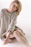 Kleedde de blonde jonge vrouw zich in grote witte kasjmiersweater en plaatsing op witte geheel-vloer royalty-vrije stock fotografie
