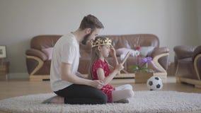 Kleedde de portret jonge knappe vader hoofd van zijn leuke kleine het langharige dochter met kroon en zij is gelukkig stock videobeelden