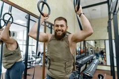 Kleedde de portret spier Kaukasische gebaarde mens zich in gewogen vest in de gymnastiek, militaire stijl stock afbeelding