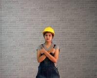 Kleedt de de waren gele helm van de technicusvrouw met grijze T-shirt en denimjeansschort de status van en duimen omhoog twee han stock foto