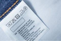 Kleedt etiket met de instructie van de wasserijzorg, sluit omhoog stock foto's