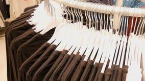 Kleedt het hangen op hangers van een grote ronde tribune in een kledingsopslag in wandelgalerij of winkelcentrum stock video