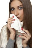 Kleenex. Sick young woman with a kleenex in hand Royalty Free Stock Photography