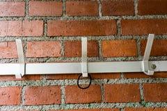 Kleerhanger op bakstenen muur met hairband stock foto's