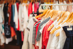 Kleerhangers met kleurrijke kleren in een vrouwenwinkel De verkoop van de zomer Stock Afbeelding