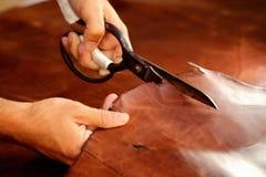 Kleermaker die dierlijke huiden, leer bij textielfabriek snijden Royalty-vrije Stock Foto's