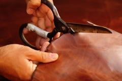 Kleermaker die dierlijke huiden, leer bij textielfabriek snijden Stock Afbeelding