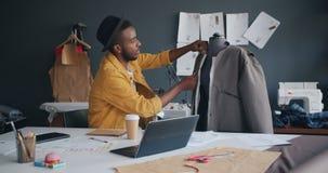 In kleermaker die kledingstuk op model meten die dan in notitieboekje het werken schrijven stock video