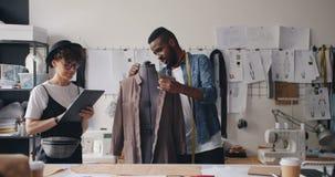 Kleermaker die kleren op ledenpop meten terwijl meisjescollega die met tablet werken stock video