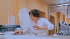 Kleermaker die met patroon van nieuwe kleermakerijeninzameling werken stock videobeelden