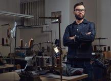Kleermaker die zich dichtbij lijst met naaimachine bevinden en bekijkend een camera in een naaiende workshop royalty-vrije stock foto