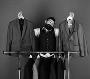 Kleermaker met een kostuum Het concept van de manierkeus Mens met baard door klerenrek stock foto