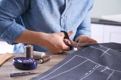 Kleermakers scherpe stof bij lijst in atelier Royalty-vrije Stock Afbeeldingen