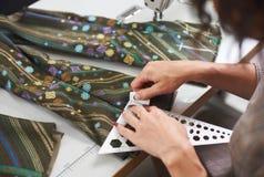 Kleermakerswerkplaats: vrouwelijke handen die noteringen op kledingstukdetails maken alvorens op naaimachine te naaien stock afbeelding