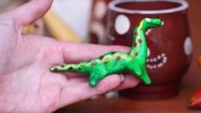 Klei ceramische stuk speelgoed de handverf van dinosaurus mooie leuke jonge geitjes, vernis stock videobeelden