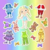 Kleiden Sie eine nette Puppe mit Sätzen Kleidung mit Zubehör und Spielwaren Stockfoto