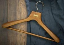 Kleiderbügel mit Anzug auf hölzernem Brettwäschereishop-Geschäft concep Lizenzfreie Stockbilder