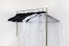 Kleidersäcke und Aufhänger sind auf Gestell Stockbilder