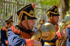 Kleideten Männer in einer alten Militäruniform an, welche die Trompete spielt lizenzfreies stockbild