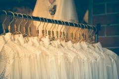 Kleidung arbeitet auf Aufhängern am Bekleidungsgeschäft um Mit Weinlesefilter Lizenzfreie Stockfotos