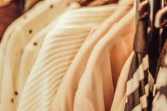 Kleidung, die am Aufhänger im Speicher hängt stockbilder