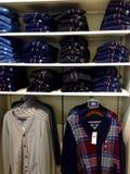 Kleidung, die an den Aufhängungen hängt Stockbild