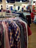 Kleidung, die an den Aufhängungen hängt Lizenzfreie Stockfotografie