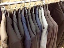Kleidung, die an den Aufhängungen hängt Lizenzfreie Stockfotos