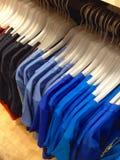 Kleidung, die an den Aufhängungen hängt Lizenzfreies Stockbild