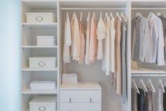 Kleidung, die an der Schiene in der weißen Garderobe hängt Lizenzfreie Stockfotografie