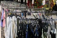 Kleidung, die an einem Aufhänger in einem Markt im Freien Asprovalta, GR hängt Lizenzfreie Stockfotografie