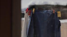 Kleidung, die an einem Seil und an einem Trockner hängt stock footage