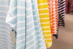 Kleidung, die an einem Speichergestell hängt Lizenzfreie Stockbilder