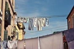 Kleidung, die heraus an einer traditionellen Venedig-Straße hängt Stockbilder