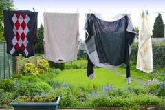 Kleidung, die von waschender Zeile hängt Lizenzfreie Stockbilder