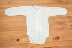 Kleidung für neugeborenes Mädchen auf einem hölzernen Hintergrund Stockfotografie