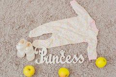 Kleidung und Schuhe für Babys und Äpfel Lizenzfreies Stockbild