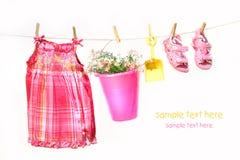 Kleidung und Spielwaren des kleinen Mädchens auf einer Wäscheleine Lizenzfreies Stockbild