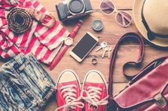 Kleidung und Zubehör für Frauen auf Holzfußboden Stockfotografie