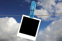 Kleidungsklammer mit leerem polaroidfeld Stockbild
