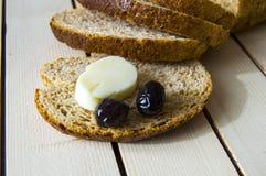 Kleiebrot und außer schwarzen Oliven, Käse, dem schönsten Frühstückskäse und den schwarzen Oliven Im unterschiedlichen Konzeptbro Stockfoto