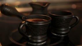 Kleikoffie vastgestelde Cezve en twee koppen met het stomen coffe stock videobeelden