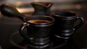 Kleikoffie vastgestelde Cezve en twee koppen met het stomen coffe stock video