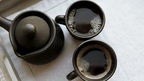 Kleikoffie vastgestelde Cezve en twee koppen met het stomen coffe stock footage