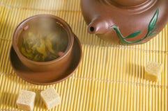 Kleikop en theepot met groene thee en rietsuikerkubussen op een bamboemat Royalty-vrije Stock Afbeeldingen