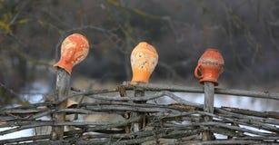 Kleikruiken op een houten omheining stock afbeeldingen